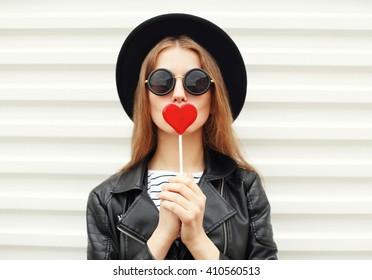 Mode portrait jolie douce jeune femme s'amusant avec sucette sur fond blanc