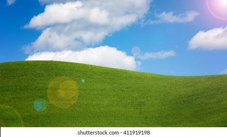 緑の野原と明るい雲と青い空