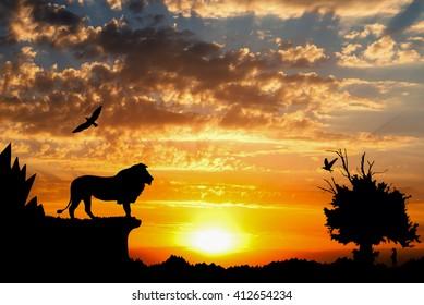 Jungel med fjell, gammelt tre, fugle løve og surikat på gylden overskyet solnedgang bakgrunn