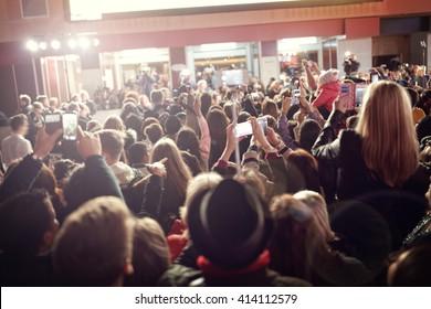 レッドカーペットの映画プレミアで携帯電話で写真を撮る群衆とファン