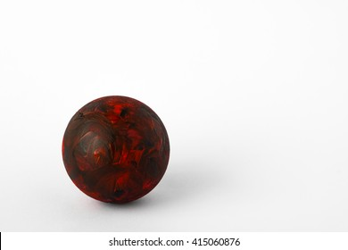 The sphere painted with red and black on white background. It look like a lava planet.