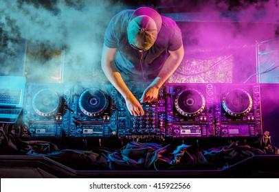 Charismatischer Discjockey am Plattenteller. Während der Party spielt der DJ auf den besten und bekanntesten CD-Playern im Nachtclub. EDM, Partykonzept.