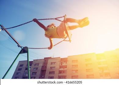 Kleines Mädchen, das auf Schaukel im Stadthaushof fliegt. Kindheit, Freiheit, glücklich, Sommer im Freien
