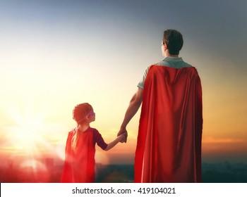 Gelukkig liefdevolle familie. Vader en zijn dochter kind meisje buiten spelen. Papa en zijn dochtertje in de kostuums van een superheld. Concept van Vaderdag.