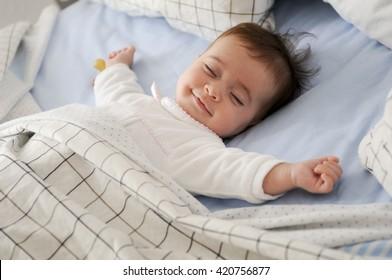 青いシーツで寝ているベッドに横たわって笑顔の女の赤ちゃん