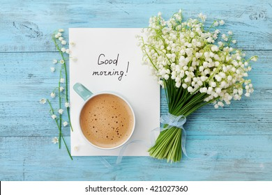 Coffee mug with bouquet of flowers lily of the valley and notes good morning on turquoise rustic table from above, beautiful breakfast, vintage card, top view, flat lay