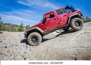 カリフォルニア州タホ湖近くのルビコントレイルの急な岩を下る4x4トラック。