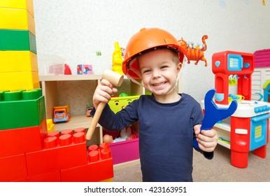 Lustiger kleiner Handwerker mit Spielzeughammer und Schraubenschlüssel in der Kindertagesstätte