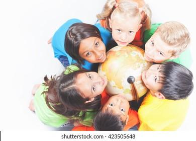 Gruppe von internationalen glücklichen Kindern, die Globus Erde halten und in die Kamera schauen. Schulkinder lernen Geographie. Multiethnische Menschen. Welt. Ökologie. Reine Erde. Internationaler Kindertag