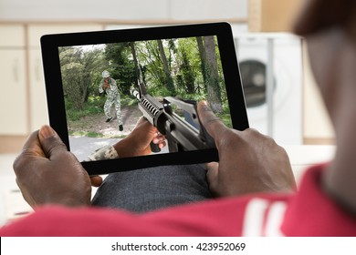 Close-up Of A Man Playing Action Game On His Digital Tablet
