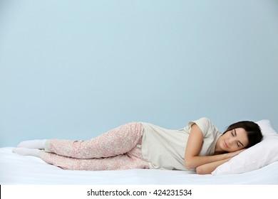 青の背景にベッドで寝ているパジャマの若い女性