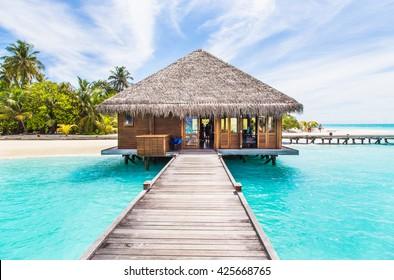 Wasservillen (Bungalows) auf der perfekten tropischen Insel, schöner weißer Sand am blauen Wasserblauen Himmel des tropischen Strandes mit Kokospalme, Malediveninseln