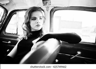 ビンテージ車の上に座ってレトロなスタイルで明るい化粧品で美しいファッションの少女モデルの肖像画