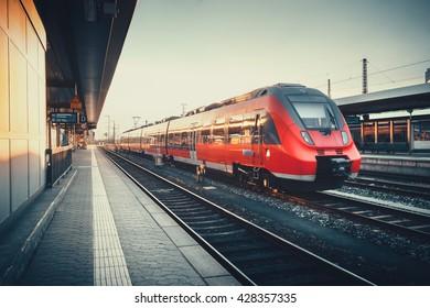 ドイツ、ニュルンベルクのカラフルな夕日にモダンな赤い通勤電車のある美しい鉄道駅。ヴィンテージ調色の鉄道