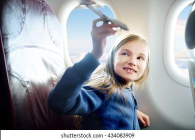 飛行機で旅行する愛らしい少女。飛行機の窓際に座っておもちゃの飛行機で遊んでいる子供。