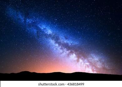 Nachtlandschaft mit bunter Milchstraße und gelbem Licht an den Bergen. Sternenhimmel mit Hügeln im Sommer. Schönes Universum. Raumhintergrund