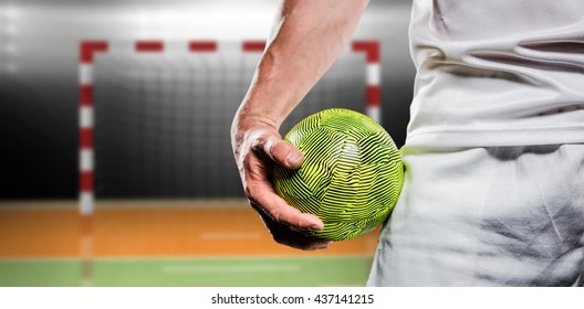 Sportsman holding a ball against digital image of handball goal
