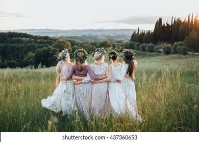 ドレスと花と緑の花輪の女の子は日没時に緑の野原にいます