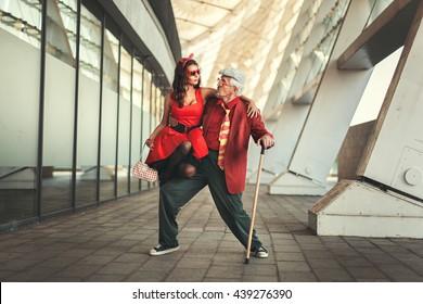 若い女の子は老人と踊っていて、レトロな服を着ています。
