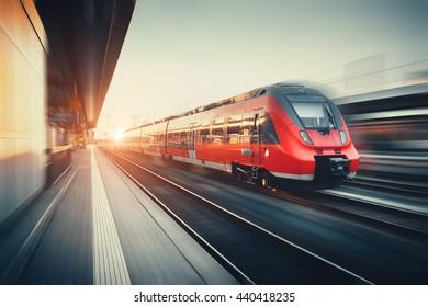 ドイツ、ニュルンベルクのカラフルな夕日にモーションブラー効果のあるモダンな高速赤い通勤電車のある美しい鉄道駅。ヴィンテージ調色の鉄道
