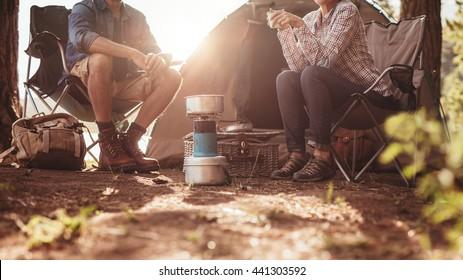 テントの外の椅子に座っている男性と女性のトリミングされた画像。森でキャンプするカップル。