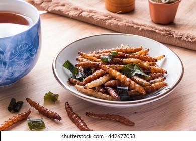 木製のテーブルの背景にお茶と皿にパンダン、タイペッパーパウダーを混ぜた竹虫の食用昆虫クリスピー。揚げ虫はタイで人気のスナック食品です、クローズアップ、水平方向の画像