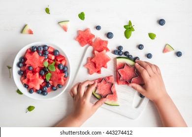 Wassermelonensalat. Wassermelonenscheiben in Form eines Sterns. Kinderhände, die Obstsalat auf weißem Tisch kochen. Draufsicht, flach liegen