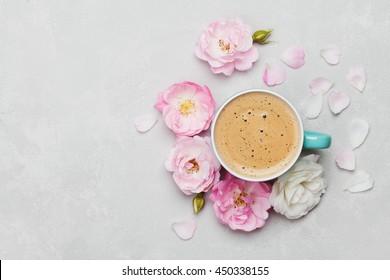 Morgen Tasse Kaffee und eine schöne Rosenblumen auf hellem Hintergrund, Draufsicht. Gemütliches Frühstück. Flacher Laienstil.