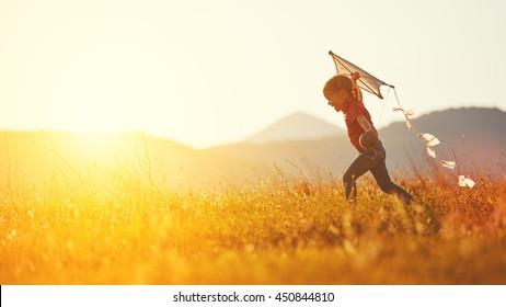 Niña niño feliz con una cometa corriendo en la pradera en verano en la naturaleza