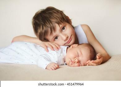 bebé en pijama blanco durmiendo boca abajo, su hermano mayor abraza