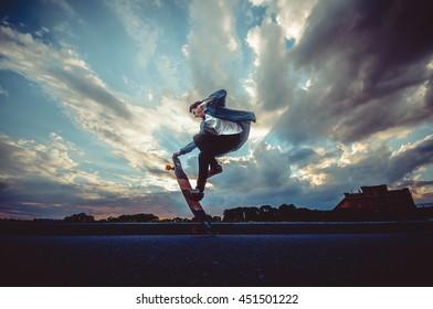 通りでスケートボードでスケーター作りのトリック。ロングボードでカジュアルウェアの男性。屋外の雲と広い青い空を背景。極端なスポーツコンセプト。テキストまたはロゴのスペースをコピーします。