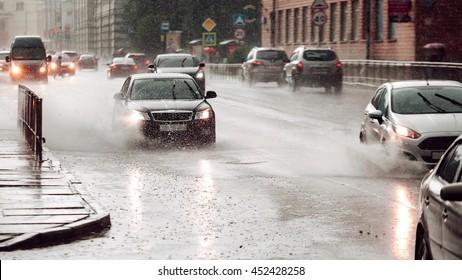 Rápida velocidad. El automóvil en movimiento forma un charco cuando la lluvia cae sobre el concreto. Pantalla ancha