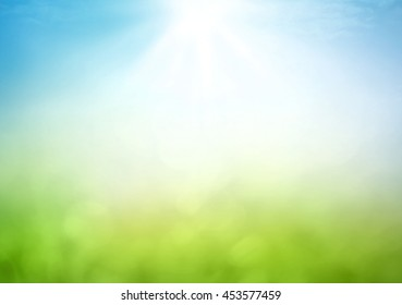 Concepto del día de la tierra: desenfoque abstracto hermoso prado de luz verde suave bokeh y cielo azul sobre fondo de amanecer de otoño