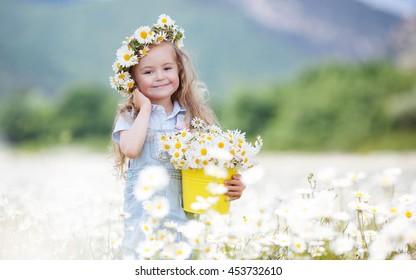 カモミールフィールドでかわいい笑顔の女の子。カモミールで頭に花輪を捧げる小さな金髪の子供の女の子