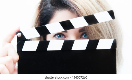 Young blue eyes blonde woman actress close up with movie clapper behind face