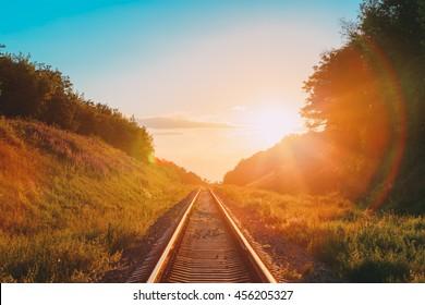 El paisaje escénico con el ferrocarril que va directamente a través de la pradera montañosa de verano hasta el atardecer o el amanecer en la luz del sol. Efecto destello de lente.