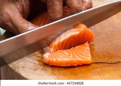 Mano y dedos El chef japonés usa un cuchillo afilado que corta salmón fresco para sushi de sashimi. Estilo de comida tradicional japonesa para una buena salud.