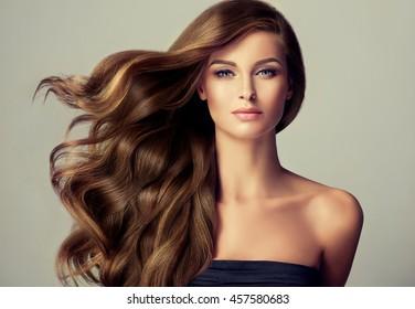 Brünettes Mädchen mit langen und glänzenden gewellten Haaren. Schönes Modell mit lockiger Frisur.