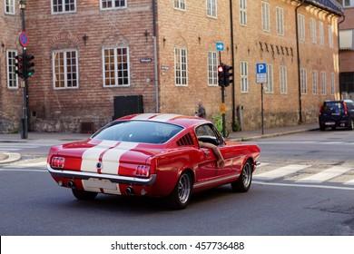 ノルウェーのオスロの旧市街にあるれんが造りの家の前にあるヴィンテージのスタイリッシュな赤い車。通りの古い車の後部の眺め。