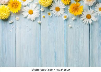 Gartenblumen über blauem Holztischhintergrund. Hintergrund mit Kopierraum