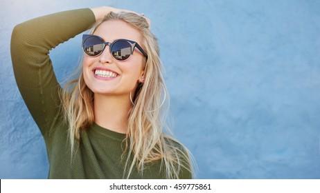 Primer plano de mujer joven con estilo en gafas de sol sonriendo sobre fondo azul. Modelo de mujer hermosa con espacio de copia.