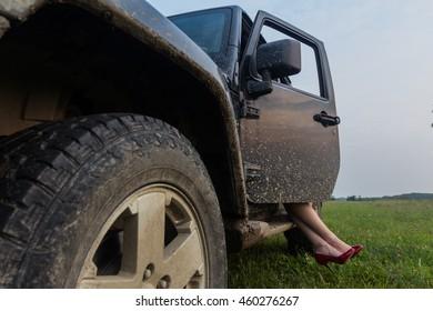das Mädchen in roten Schuhen hinter dem Lenkrad eines SUV
