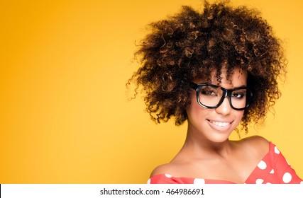 美しいアフリカ系アメリカ人の若い女性の笑顔の肖像画。眼鏡をかけているアフロの女の子。黄色の背景。スタジオショット。
