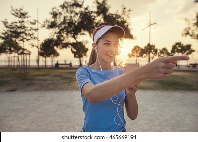 Beautiful young woman is using an app in her smartphone device to play a gps based augmented reality mobile game in the park, pointing to a direction of a possible reward