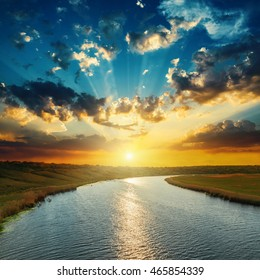 sunset with clouds, light rays over river with reflections
