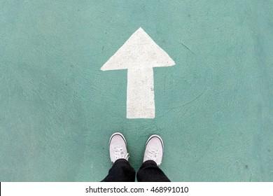 zapatos de pie en el piso de concreto y señal de dirección blanca para seguir adelante