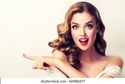 女性の驚きを示す製品。巻き毛の側を指している美しい少女。製品を紹介する。白い背景で隔離されました。表情豊かな表情