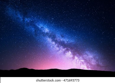 Milchstraße und rosa Licht in den Bergen. Nacht bunte Landschaft. Sternenhimmel mit Hügeln im Sommer. Schönes Universum. Weltraumhintergrund mit Galaxie. Reisehintergrund