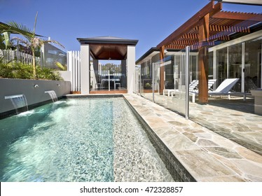 Modern swimming pool side with glass cover and wooden patio, the light blue water can be seen deeply beside the poolside with a wooden pillars and beams under blue sky