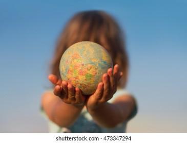 Vista frontal de la mano de un niño sosteniendo un globo de juguete dañado delante de su cara